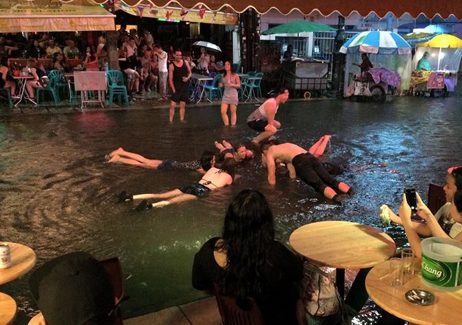 Backpackers swim in flood water on Khao San because, how often do they get to do that?